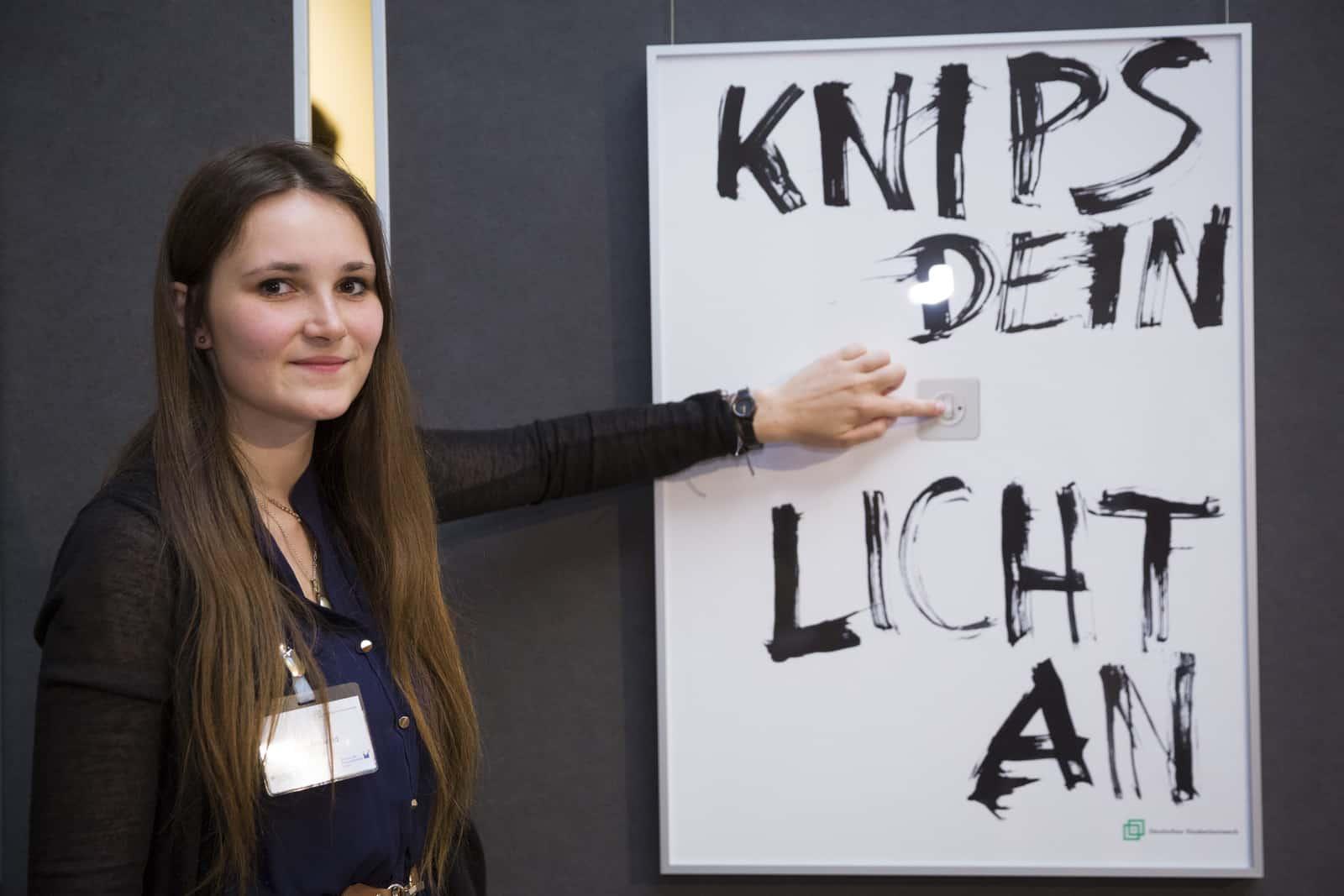 """Preisträgerin Alina Mirwald vor ihrem Siegerplakat """"Knips dein Licht an"""". Foto: Kay Herschelmann"""